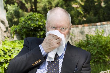 hanky: Elderly man has small relaxing break and sneezing in park