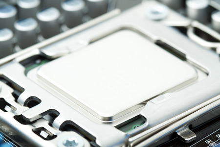 Silver computer processor in socket of motherboard photo