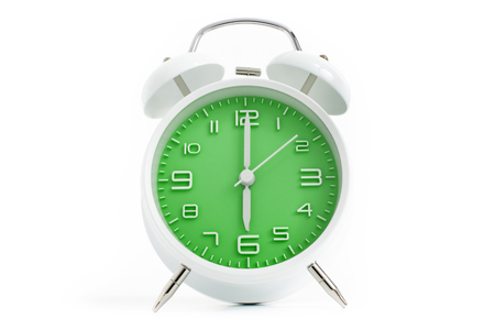 Twin bells analogue alarm clock with green clock face shows six o'clock, 6 AM PM; concept on white background