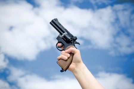 Revolver in der Hand gegen den blauen Himmel