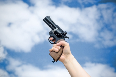 Revolver in hand against blue sky