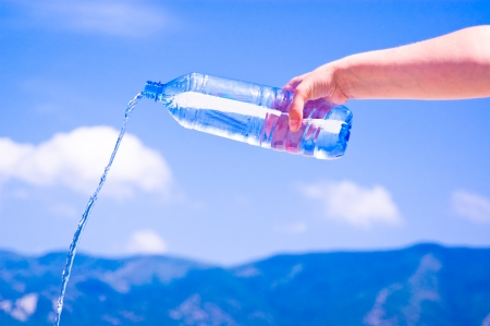 Water following from bottle on sky  Stock Photo