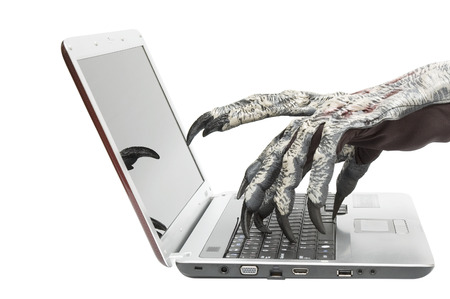 Claws of monster typing on laptop keyboard