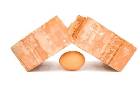 Fragile egg breaks brutal brick Stock Photo
