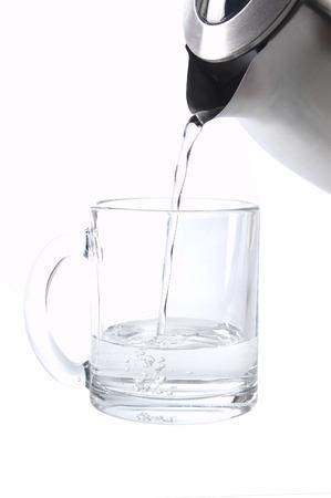 Gießt Wasser aus Wasserkocher