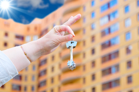 downpayment: Hand holding  keys on new house  background
