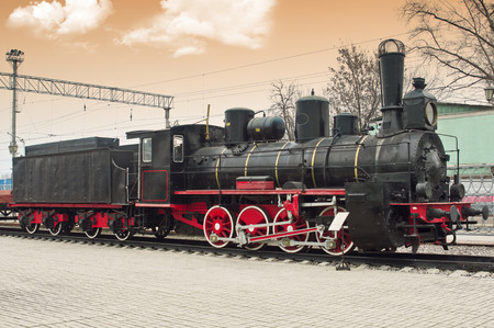 Old steam locomotive at railway station photo