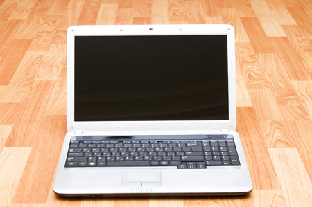 Modern laptop on wooden floor photo