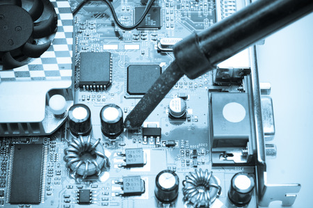 Technician repairing microprocessor with soldering iron photo