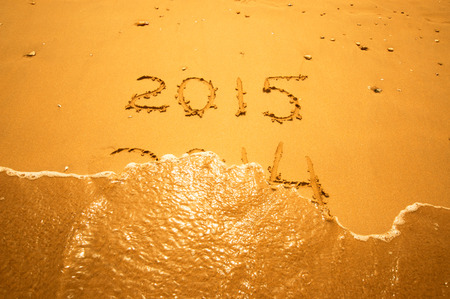 New Year 2015 is coming concept - inscription 2014 and 2015 on a beach sand, the wave is starting to cover the digits 2014  photo