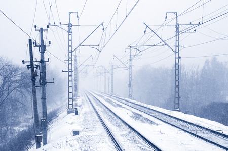 forest railroad: Empty electric railroad in winter forest Stock Photo