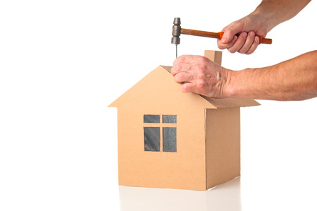 builds: Man builds cardboard model of a house