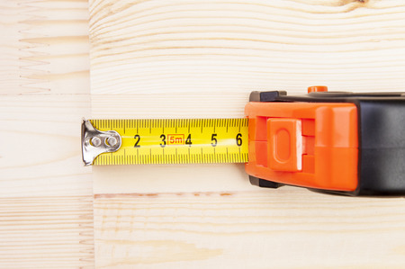 wooden metre: Measuring tape on a wood plank