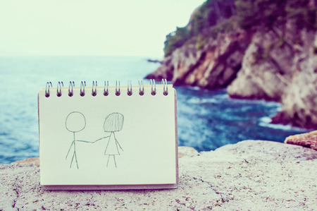 Couple drawing in notebook against seascape photo