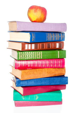 bibliophile: Stack of old books and an apple on white background Stock Photo