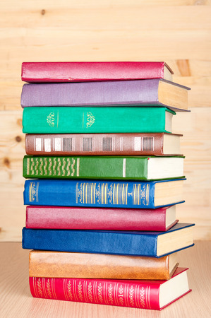 Stack of old books on wooden shelf