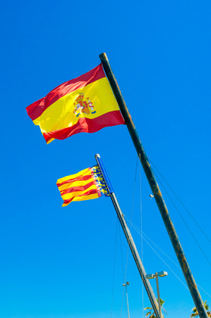 autonomic: Flags of Valencia and Spain against blue sky Stock Photo