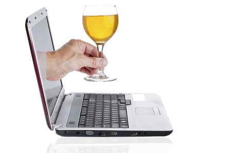 goblet: Hand with goblet with wine comes from the laptop screen Stock Photo