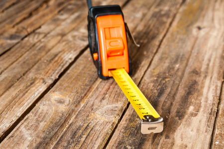 Tape measure closeup on wooden background