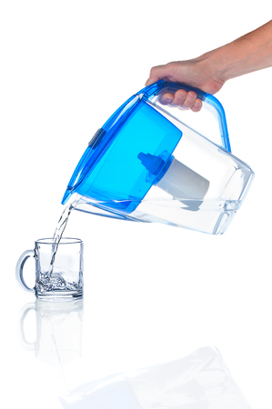 Pouring water in glass from water filter pitcher Archivio Fotografico