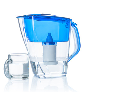 Water filter pitcher and glass on white background