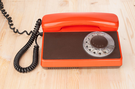 antique phone: Orange antique phone on wooden desk Stock Photo