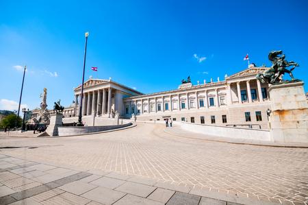 austrian: Austrian Parliament and Athena monument in Vienna against blue sky