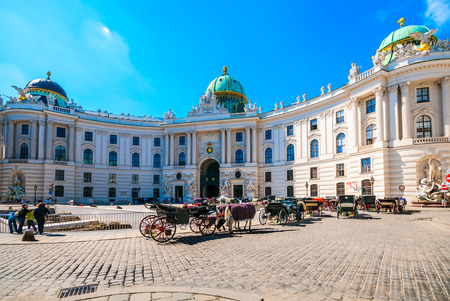 Michaelerplatz and Hofburg Palace with tourists in Vienna, Austria