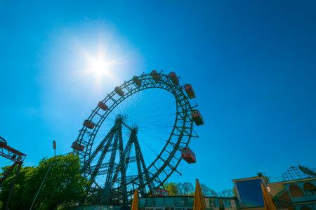 prater: VIENNA, AUSTRIA - APRIL 20, 2016: Giant Ferris Wheel against bright sun in Prater Park