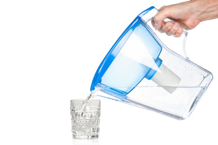 Hand holding water filter and pouring clear water in crystal glass isolated on white background