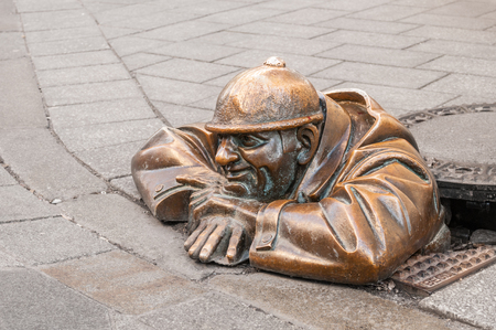 BRATISLAVA, SLOVAKIA - DECEMBER 16, 2016:  Bronze sculpture Cumil (The Watcher) or Man at work in old town Editorial