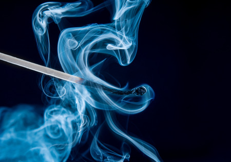 Match brûlé avec de la fumée magique sur fond noir Banque d'images