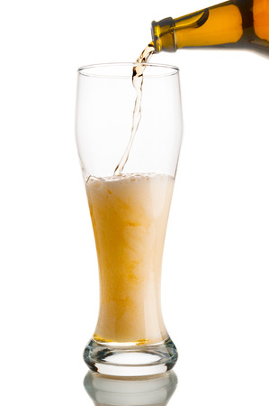 Beer pouring from bottle into glass isolated on white background Stock Photo