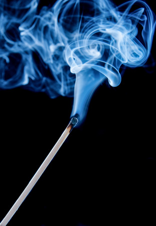 Match with blue smoke on black background