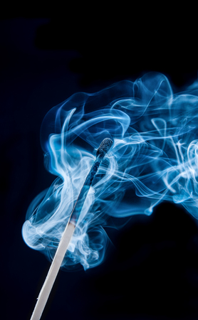Burnt match in blue smoke on black background