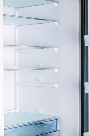 Empty open fridge with shelves Standard-Bild