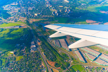 Wing of airplane flying above of the town