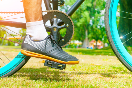 Male`s foot on pedal bicycle in a park at summer Stock Photo