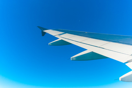 Airplane wing in the clean blue sky