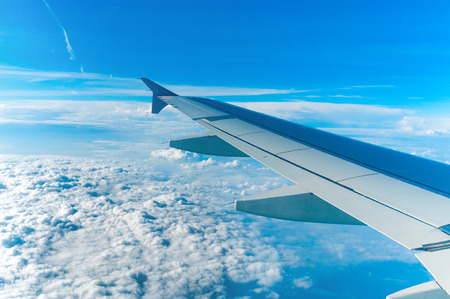 Wing of aircraft flying above the clouds Stock Photo