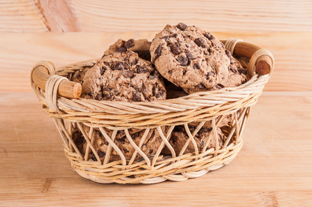 Cookies in wicker basket on wooden background