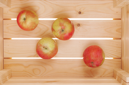 Few apples in wooden box close up Stock Photo