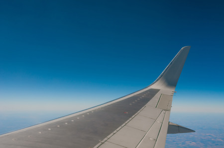 Airplane wing flying in blue sky