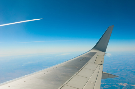 View from window on plane wing and aircraft trail