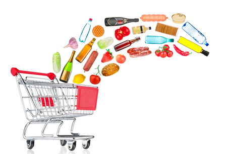 Different food products falling into shopping cart on white background