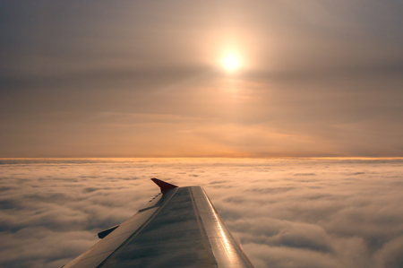 Wing of plane flying above on clouds
