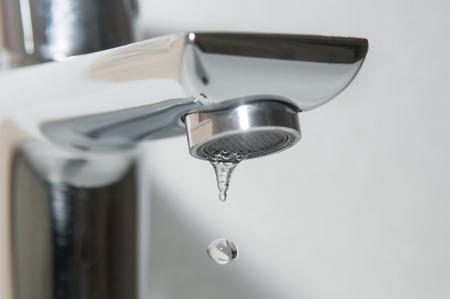 Bath faucet and falling water drops close up