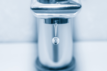 Faucet with water drops on blue background