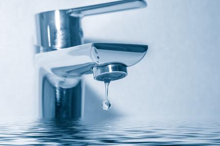 Wasserhahn mit Wassertropfen hautnah auf blauem Hintergrund Standard-Bild