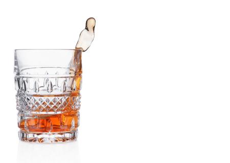 Splashing whiskey in crystal glass isolated on white background